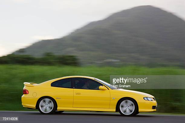 Holden Monaro car passes a sugar cane field at Freshwater Connection Australia