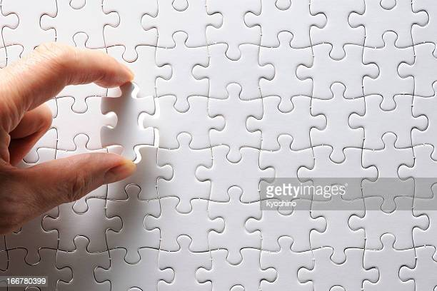 Holding a blank final piece of the jigsaw