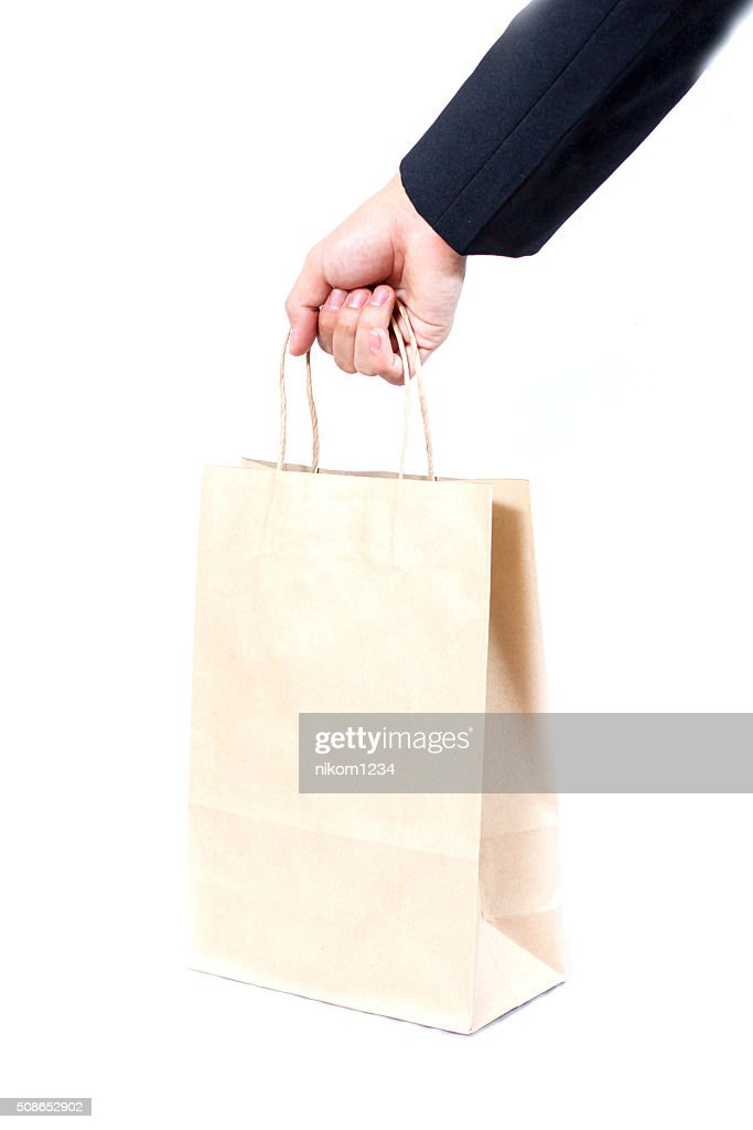 holding a brown paper bag with contents in his hand : Stock Photo