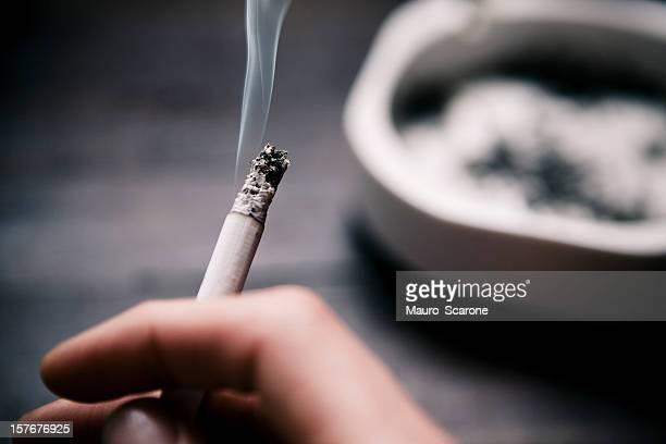 Sosteniendo un cigarrillo.