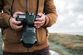 Two hands holding a modern DSLR camera.