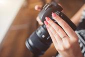 Woman hands holding dslr camera.