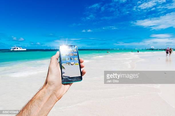 Hält ein smartphone in der Karibik in Punta Cana, Dominikanische Republik