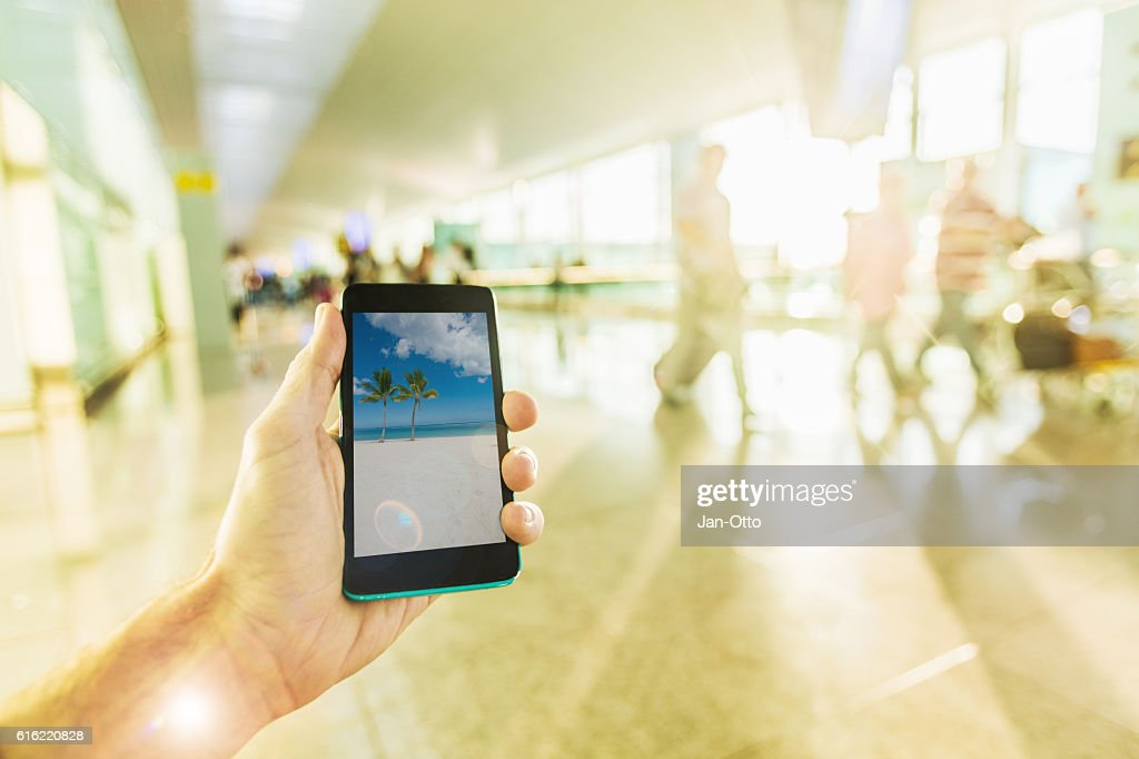 Holding a smartphone on airport : ストックフォト