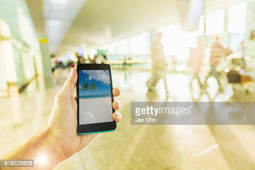 Holding a smartphone on airport : Stock Photo