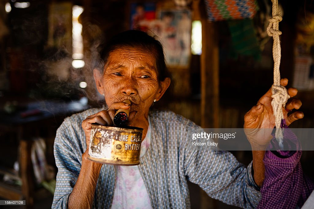 Holding a tin can under a handrolled cheroot to catch ash an old woman relaxes in her house in Minanthu village near Bagan Hand rolling and smoking...