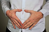 Holding an IUD birth control copper coil device over the uterus with hands in heart shaped form, used for contraception