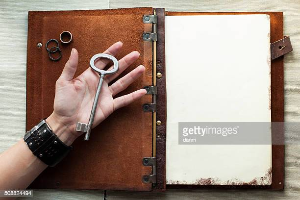 Holding an old key over a book