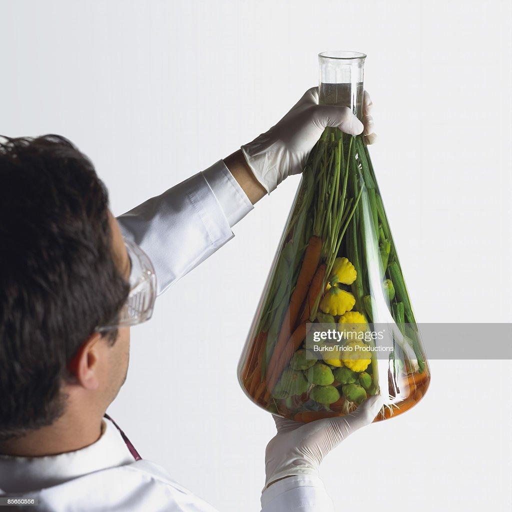 Holding beaker of vegetables : Stock Photo