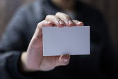 Man is holding a blank white card.