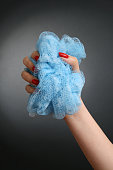 Woman hand holding blue loofah isolated in black background