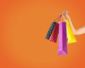 Holding fancy shopping bags on orange background