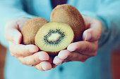 holding fresh kiwi fruit in hands vintage tone