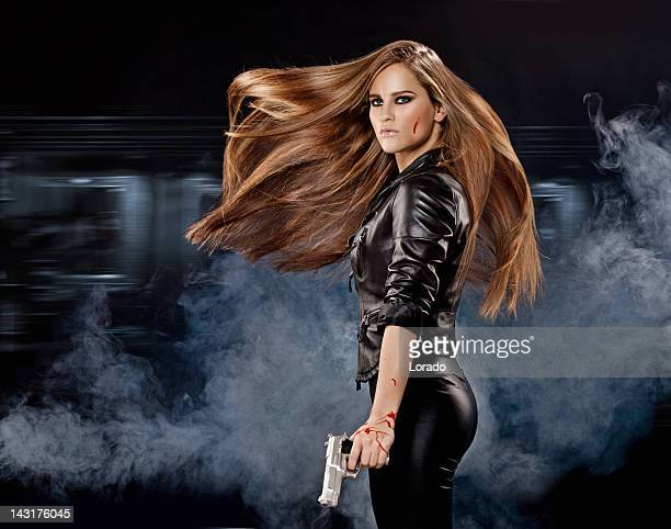 Holding gun sexy woman with long flying hair