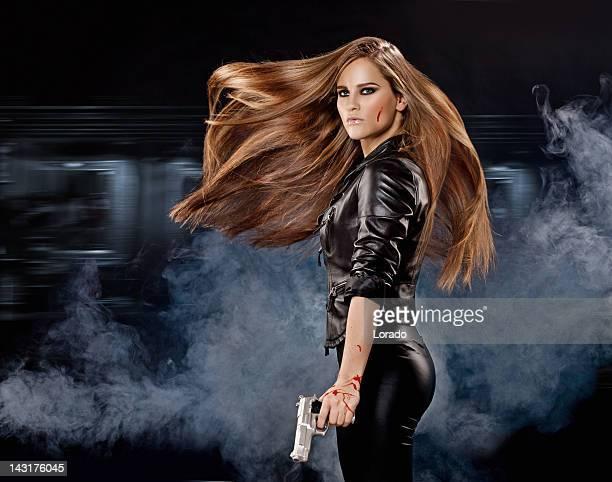 Tenant gun sexy femme avec de longs cheveux de vol