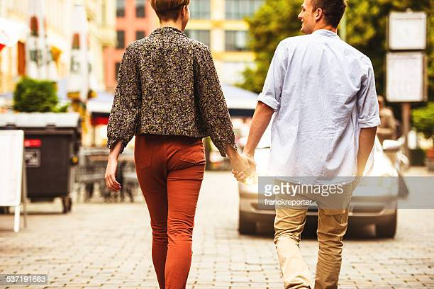 Holding hands, caucasian couple in love on the city