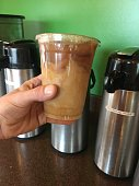 Holding up my ice coffee my daily routine. Male hand holding up ice coffee drink