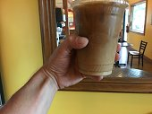 Holding up my ice coffee my daily routine. Male hand holding up ice coffee drink with a mirror in background