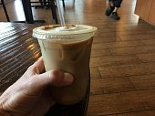Holding up my ice coffee my daily routine. Male hand holding up ice coffee drink on a coffee table