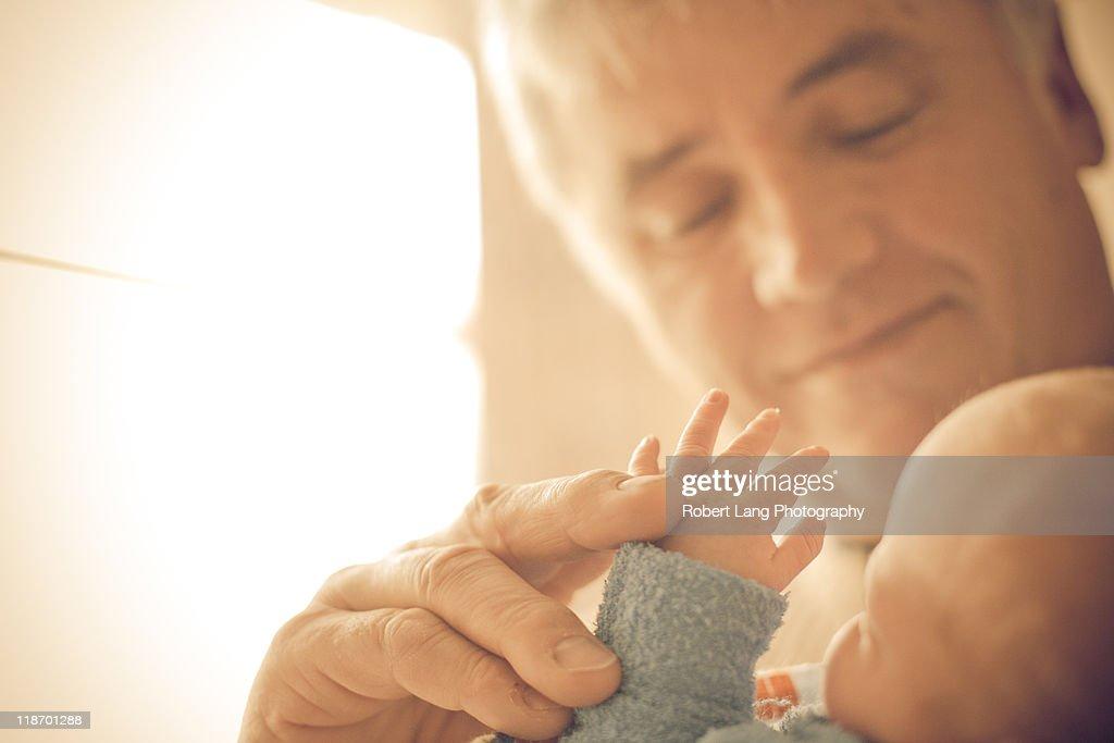 Holding new born grandchilds hand : Stock Photo