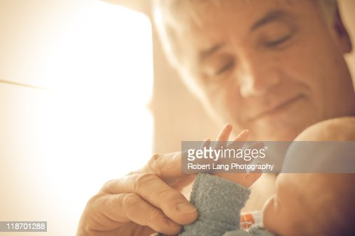 Holding new born grandchilds hand
