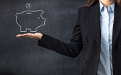 Businesswoman holding piggy bank drawing front of blackboard