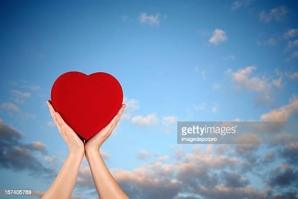 holding red heart over sky