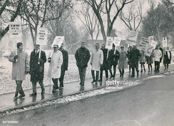 Holding their Picket Signs High A Band of Men and Women Teachers March Outside Hill Junior High School Denver's junior and senior high schools were...