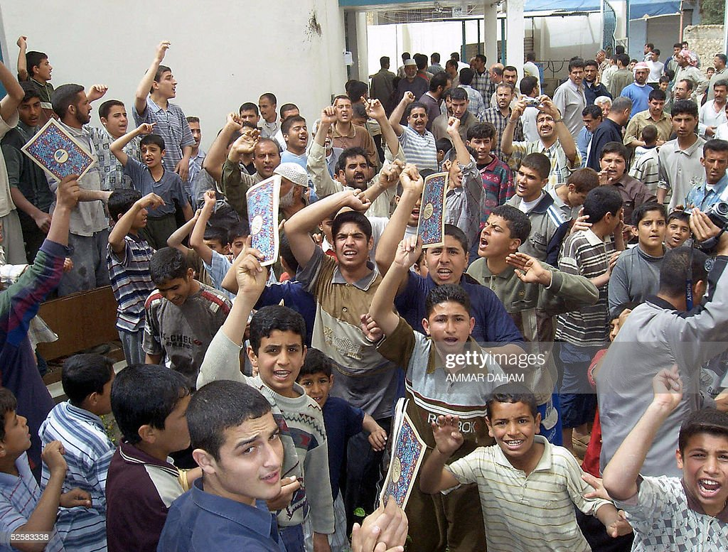 Holding up books with Islamic covers people protest outside the Aziz alHakim mosque in the city of Ramadi 100 kms west of Baghdad 03 April 2005 The...