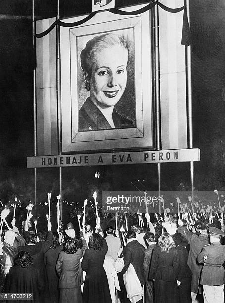 Holding up lighted candle torches Argentinians gather around a portrait of Eva Peron in Buenos Aires to mourn the late first lady