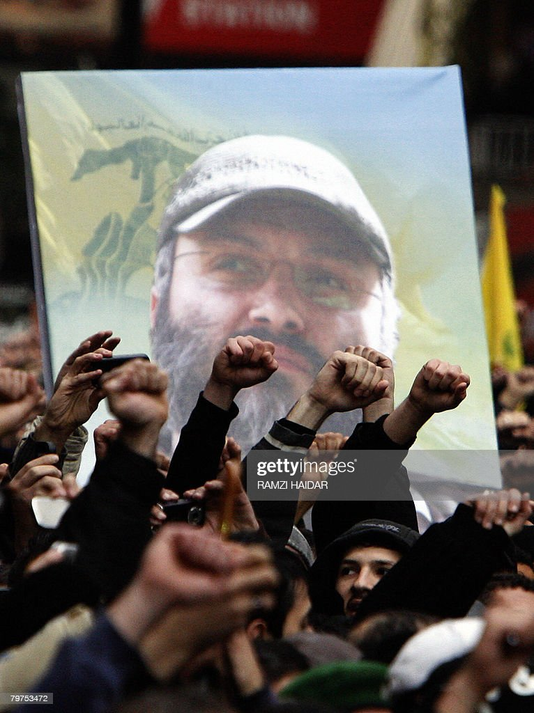 Holding up the image of assassinated Hezbollah commander Imad Mughnieh mourners take to the streets during his funeral in Beirut's mainly Shiite...
