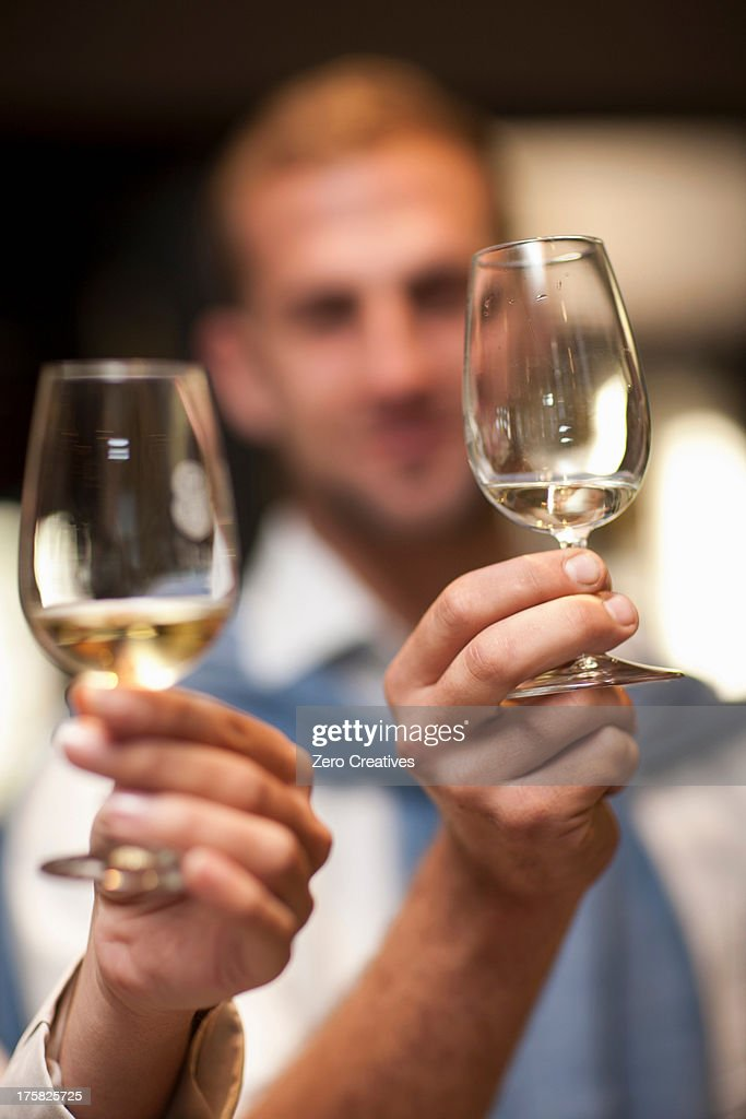 Holding up wine glass to check colour of wine