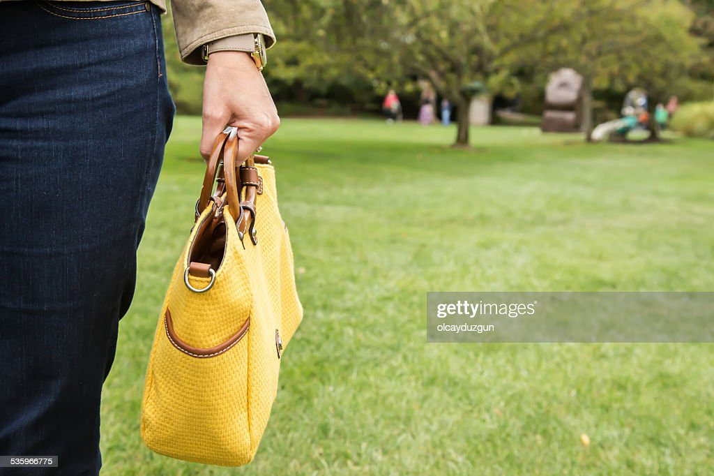 Holding yellow purse : Stock Photo