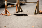Hole in asphalt on automotive roadway street. Pit in road surface, is surrounded by building fence construction with warning tape for motorists. Repair of pavement or road surface