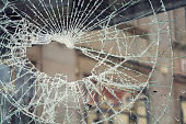 Hole in broken shattered security glass, insurance, security, vandalism or crime concept