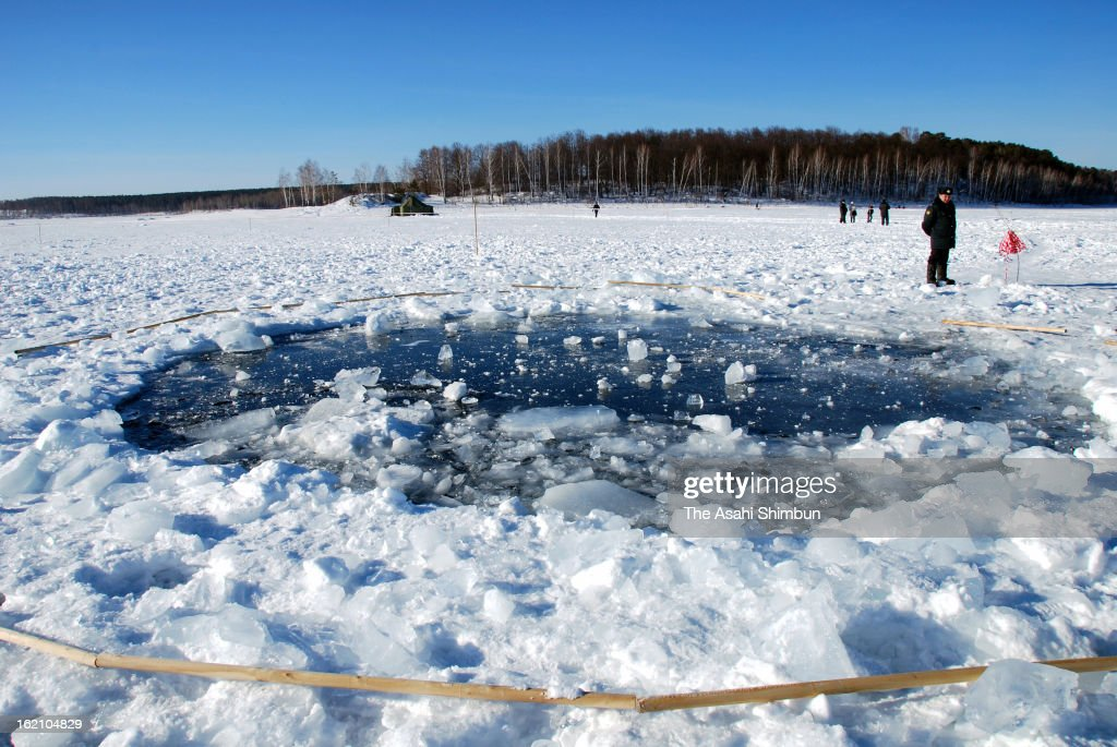 A hole, thought to be made by the fragment of the meteor in the ice of Chebarkul Lake is seen on February 16, 2013 some 80 kilometers from Chelyabinsk, Russia. Local government reported more than 1,100 people injured, mostly by flying glass broken by the shock wave of the meteor explosion.