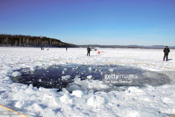 A hole thought to be made by the fragment of the meteor in the ice of Chebarkul Lake is seen on February 16 2013 some 80 kilometers from Chelyabinsk...