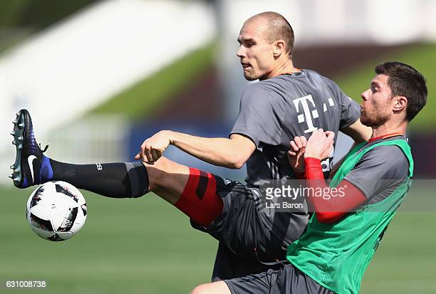 Holger Badstuber is challenged by Xavi Alonso during a training session at day 3 of the Bayern Muenchen training camp at Aspire Academy on January 5...