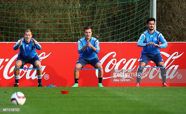 Holger Badstuber Mario Goetze and Ilkay Guendogan attend a Germany training session at Kleine Kampfbahn training ground on March 24 2015 in Frankfurt...