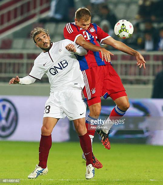 Holger Badstuber of Muenchen is challenged by Paulo Betanin of Qatar Stars during a friendly match between FC Bayern Muenchen and Qatar Stars at...
