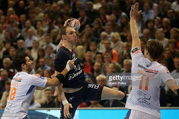 Holger Glandorf of Flensburg is challenged by Felipe Borges of Montpellier during the Velux EHF Champions League round of 16 second leg match between...