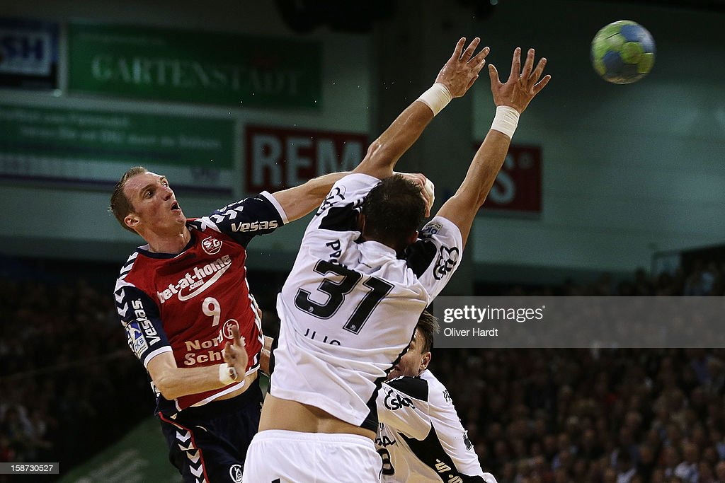 Holger Glandorf (L) of Flensburg is challenged by Momir Ilic (C) of Kiel during the DKB Handball Bundesliga match between Flensburg-Handewitt and THW Kiel at Campus Hall on December 26, 2012 in Flensburg, Germany.