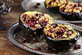 Acorn squash stuffed and baked with butter, brown sugar, walnuts and cranberries, ready for holiday dinners. Extreme shallow depth of field with beautiful bokeh. FoodLove2014