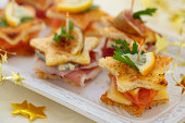 'Star shaped toasts with smoked salmon,procsiutto and cheese. Shallow dof.'