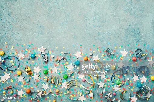 Fond de vacances décorés de confettis colorés, star, bonbons et streamer sur la vue de dessus de table bleu vintage. Style plat laïc. : Photo