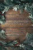 Christmas background with fir branches on wood, sprinkled with snow.