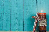 Holiday candle and wood cross with rope by antique rustic teal blue background