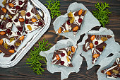 Holiday chocolate bark with dried fruits and nuts on a dark wood background. Top view. Dessert recipe for judaic holiday Tu Bishvat