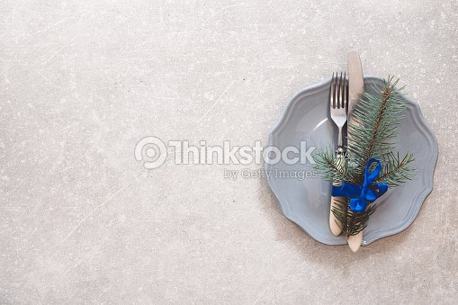 Holiday Christmas food background, cutlery, plate and Christmas tree branch, gifts on a stone background