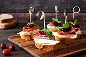 Holiday crostini skewers with cranberry sauce, brie, salami, and mint on a wooden server